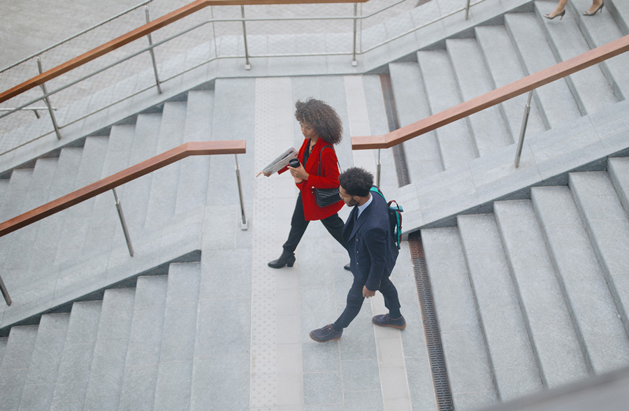 Man and woman wearing suits walking down large flight of office stairs.